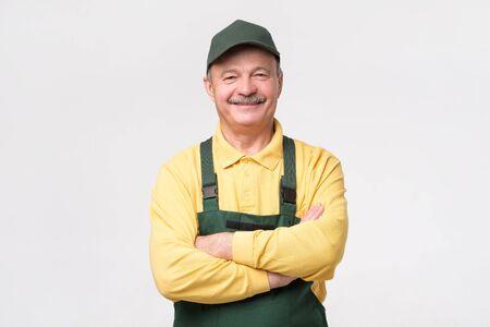 Hispanischer reifer Mechaniker in grüner Mütze und Overalls stehend mit gefalteten Händen lächelnd auf weißem Hintergrund. Standard-Bild