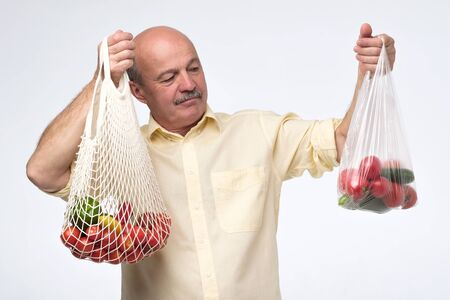 String bag versus plastic one. Mature hispanic man choosing a cotton bag for his shopping.