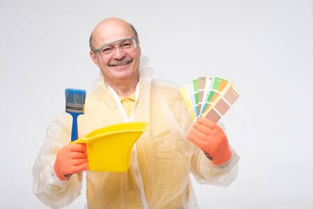 Hispanic mature painter man with color swatches in hand smiling at camera. Experienced painter is ready to do all the repair work.