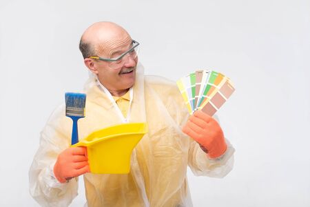 Hispanic mature painter man with color swatches in hand choosinng color for room