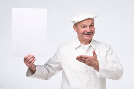 Joyful attractive hispanic mature chef cook holding copy space on his palm, looking at camera smiling, presenting new menu