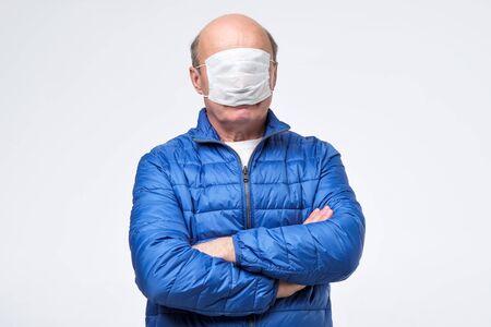 Senior man in blue jacket wearing medical mask in wrong way. Stock Photo