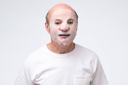 Hispanic mature man in a cosmetic mask skin care. Studio shot. take care about health at old age. Stock Photo