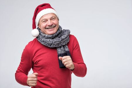 Excited senior hispanic man in red christmas cap dancing isolated on white background. Celebrate new year concept
