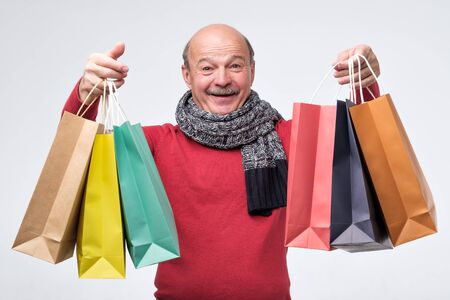 Senior hispanic man holding colored shopping bagsafter shopping in the mall. Stock Photo