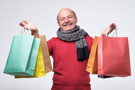 Senior hispanic man holding colored shopping bagsafter shopping in the mall. 版權商用圖片