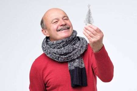 Senior hispanic man in scarf holding small silver pine tree. Concept of new year and Christmas. Studio shot