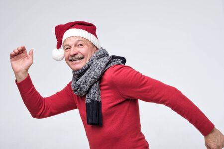 Hispanic mature man in red christmas hat is running fast. Side view. Studio shot