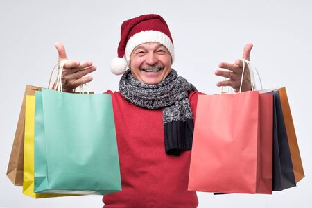 Senior hispanic man in red christmas hat holding colored shopping bagsafter shopping in the mall. Preparing for New year or Christmas.