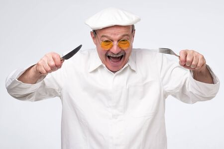 Mature hispanic man in cook unifrom and yellow glasses is hungry. Studio photo