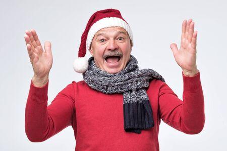 Senior hispanic happy emotional man wearing christmas santa hat showing big size. Studio shot