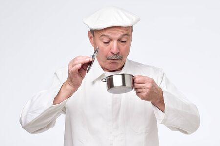 Senior chef cook holding small pan and looking inside it with surprise. Studio shot