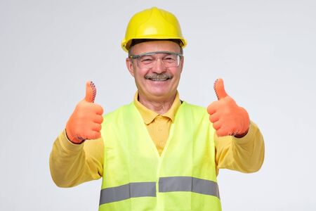 Senior hispanic construction worker in hard hat showing thumb up sign smiling on gray background