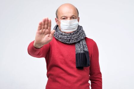 Stop the infection concept. Senior man in medical mask showing gesture stop. Health care concept.