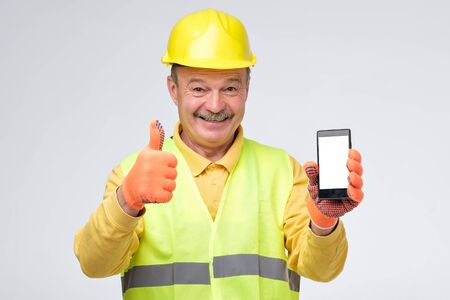 Senior hispanic guy with protective helmet on his head holding white smart phone showing thumb up approving your choice. Studio shot Stock Photo