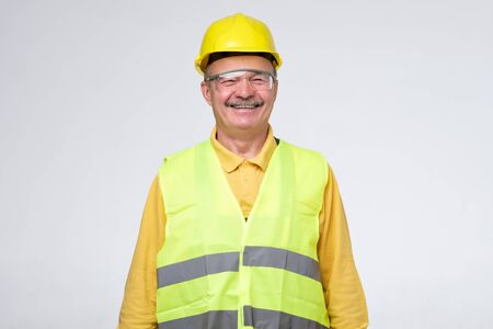 Senior hispanic construction worker in hard hat smiling on gray background. Positive facial human emotion.