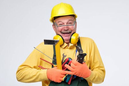 Laughing senior hispanic plumber in protective glasses, gloves and helmet holding tools in hands. Studio shot