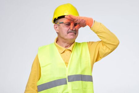 Displeased mature road worker in helmet and protective gloves closes nose because of unpleasant smell. Sewage problem.