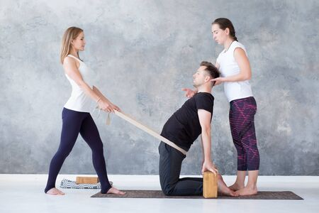 Man doing camel yoga pose in gym with his instructors
