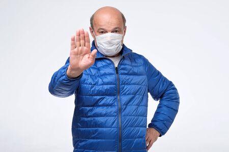 Homme senior en veste bleue portant un masque médical essayant de se protéger du panneau d'arrêt des gestes de la grippe.