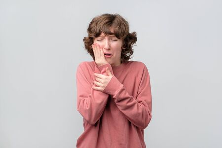 Caucasian woman in pink pullover holding her hand on her aching tooth Archivio Fotografico
