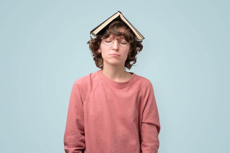 Young student in pin kpullover with book over head