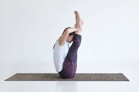 woman doing Ubhaya Padangusthasana asana, Both Big Toe pose from yoga