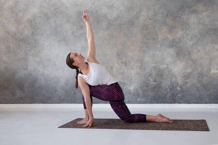 doing exercise for spine flexibility, standing in parivritta parshvakonasana