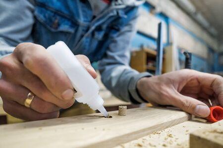 usando pegamento para conectar partes de vigas de madera.