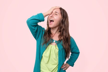 Cheerful laughing young woman touching head.
