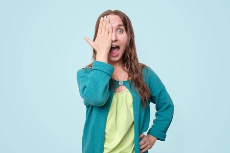 Young woman covering one eye with hand, with and surprise emotion on face.