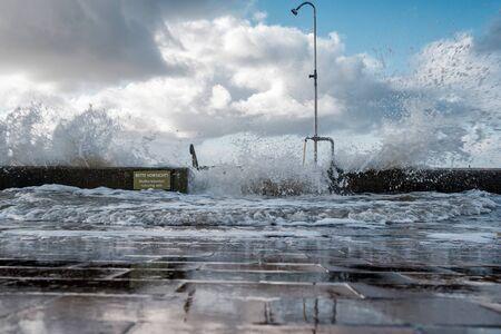 Splash of a wave on the flooded embankment near sea. It is written in german Please be careful. Steps can be slippery Stok Fotoğraf
