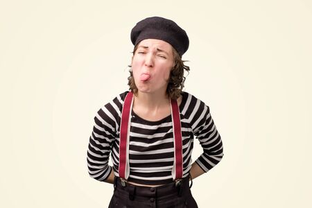 Mime young female shows tongue.