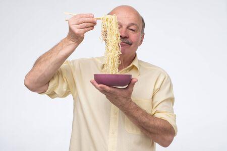 Senior man in yellow shirt eating ramen noodles.