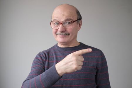 Confident hispanic senior man point aside. Serious mature male gesturing with his finger aside Stockfoto