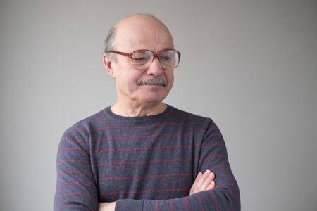 Senior hispanic man in huge glasses looking down Stockfoto - 134604462