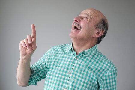 Bald mature hispanic man looking up pointing up laughing.