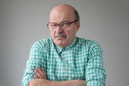 Angry senior man in glasses crossing arms looking annoyed at camera. Stockfoto - 134604546