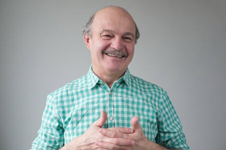 Senior hispanic man with crossed fingers smiling looking confident at camera. Positive facial human emotion.
