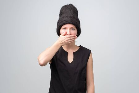 Laughing caucasian woman in black hat covers mouth with hand. Studio shot Stockfoto