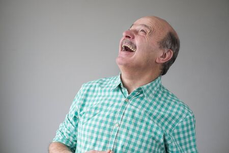 Bald mature hispanic man looking up to laughing. Positive facial human emotion