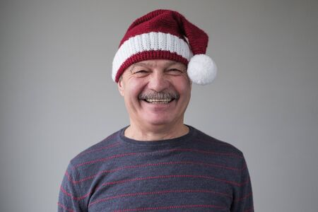 Happy senior hispanic man expressing emotions in good christmas day. Studio portrait of amazed father wears santa claus hat and blue sweater. Positive facial human emotion
