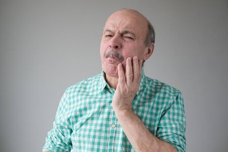 Mature spanish man feeling pain, holding his cheek with hand, suffering from bad toothache. Tooth ache concept.