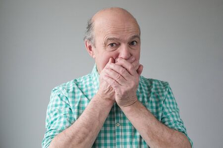 Mature senior hispanic men covering his mouth by hand Stockfoto - 134604545