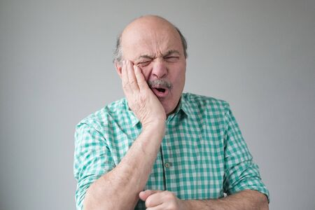 Man feeling pain, holding his cheek with hand, suffering from bad toothache Stockfoto - 134604548