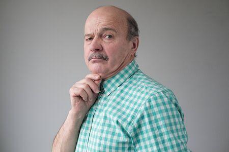 Senior bald man with a double chin looking sadly at camera. Stockfoto - 134604540