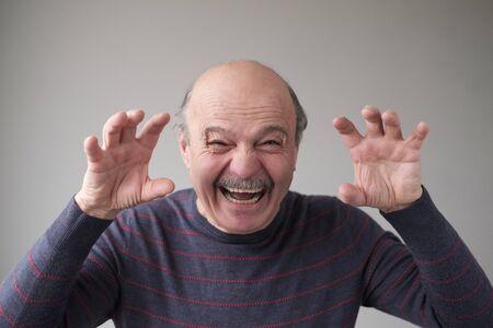 Senior hispanic man with creepy face grimacing to scare you Stockfoto - 134604553