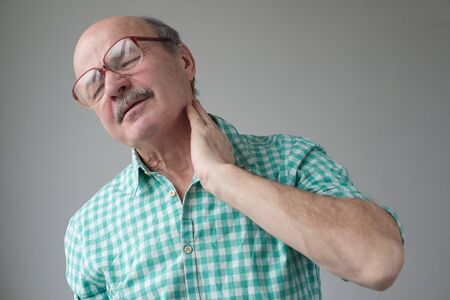 Frustrated senior holding hand on his neck while standing against grey background Stockfoto - 134604557