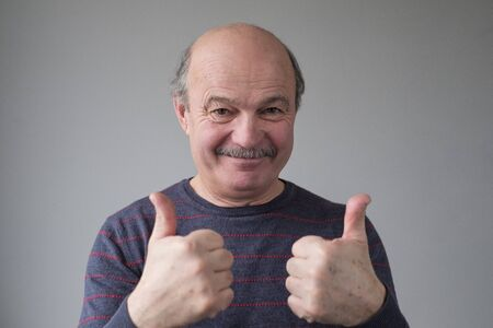 Mature man smiling showing thumb up approving your choice or giving advice. Stockfoto - 134604564