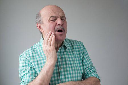 Senior hispanic bald man having terrible toothache Stockfoto - 134604566
